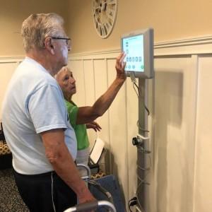 Senior stands on balance machine