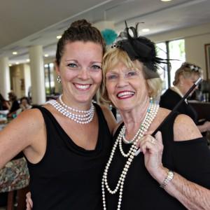 Two ladies wearing pearls hug