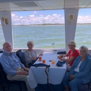 Two senior couples having meal on boat