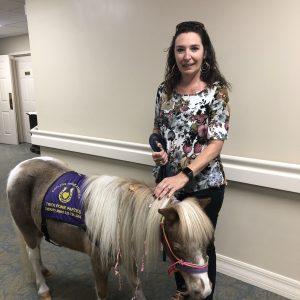 Women hold mini-horse at Arbor Glen
