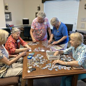 Ladies putting a puzzle together