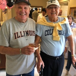 Two senior men dressed in college gear